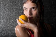 Bastante adolescente con la naranja en estudio del agua Foto de archivo