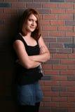 Bastante adolescente en falda del dril de algodón al lado del ladrillo wal Fotos de archivo libres de regalías