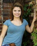 Bastante adolescente por la pared de ladrillo rústica Imagen de archivo