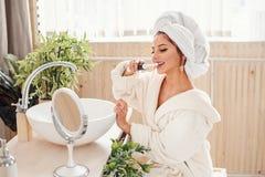 Bastante femenino cepillando sus dientes delante del espejo fotografía de archivo