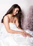 Bastante femenino en el peignoir que duerme en cama debajo de las hojas de seda Foto de archivo libre de regalías