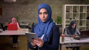 Bastante glace en mujer musulmán en el hijab azul que es permanente y que sostiene la tableta mientras que la birla en el medio d almacen de video