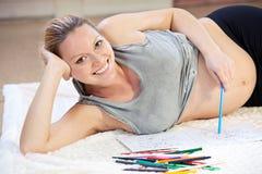Bastante gráfico de la mujer embarazada de los jóvenes con los lápices Fotos de archivo libres de regalías