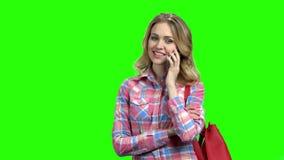 Bastante muchacha que tiene conversación telefónica en la pantalla verde almacen de video