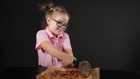 Bastante poca muchacha caucásica que corta la pizza hecha en casa deliciosa con el cortador redondo Aislado en fondo negro tirado metrajes