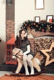 Bastante poca muchacha morena con el pelo largo que se sienta en hors de un juguete Imagen de archivo