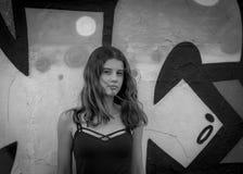 Bastante, retrato adolescente serio de la muchacha, pelo largo, fondo del grunge, blanco y negro, haciendo frente a la cámara Imagenes de archivo