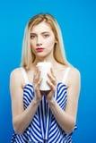 Bastante rubio con los hombros desnudos llevar el vestido rayado está celebrando la vela blanca en sus manos en fondo azul Foto de archivo