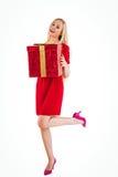 Bastante rubio en el vestido rojo que sostiene el regalo Foto de archivo libre de regalías