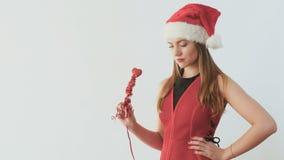 Bastante rubio en sombrero del ` s de santa crea un humor festivo con un palillo decorativo almacen de metraje de vídeo