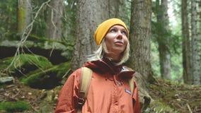 Bastante rubio en un sombrero amarillo con una mochila mira alrededor en un retrato conífero del bosque de un viajero de la mucha almacen de video