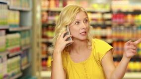 Bastante rubio haciendo una llamada de teléfono mientras que hace compras almacen de video
