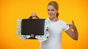 Bastante señora que señala en la cartera por completo de dinero, inversión empresarial, depósito almacen de video