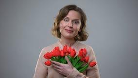 Bastante señora que sostiene las flores que sonríen en el fondo gris, regalo de vacaciones, feminidad almacen de metraje de vídeo