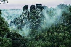 Bastei岩层,撒克逊人的瑞士国家公园,德国 与冷杉森林的有薄雾的风景行家葡萄酒减速火箭的样式的 免版税库存照片