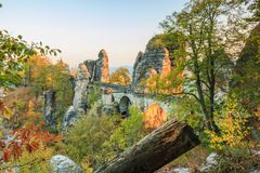 Bastei bridge in the evening sun with rock formation and tree cover in the autumn mood with old wooden trunk in the foreground stock image