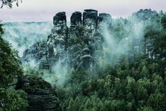 Bastei rock formations, Saxon Switzerland National Park, Germany. Misty landscape with fir forest in hipster vintage retro style royalty free stock photos