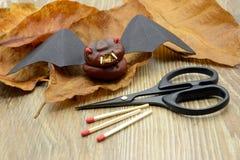 Basteln Sie die kleine Halloween-Schlägerzahl, die von der Kastanie und vom Papier gemacht wird Sc Stockbild