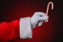 Bastão de doces da terra arrendada da mão de Papai Noel Fotografia de Stock