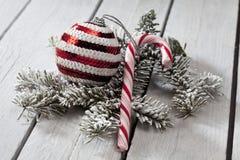 Bastão listrado da quinquilharia e de doces do Natal e galho do abeto no fundo de madeira Imagem de Stock