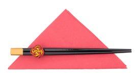 Bastoncini cinesi sul tovagliolo rosso, tovagliolo isolato su bianco Immagini Stock