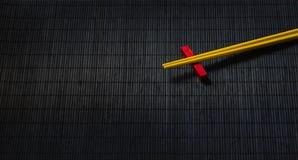 Bastoncini dei sushi sulla stuoia della paglia del bambù nero Fotografie Stock Libere da Diritti