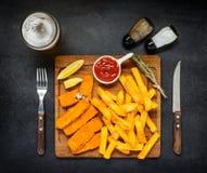 Bastoncini di pesce con le patate fritte e la birra di vetro Immagine Stock