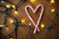 Bastoncini di zucchero che fanno un cuore con le luci bianche Fotografia Stock