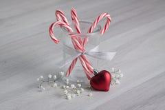 Bastoncini di zucchero con un ornamento del cuore Immagine Stock