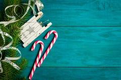 Bastoncini di zucchero di Natale, slitta del giocattolo e rami dell'abete rosso Fotografia Stock
