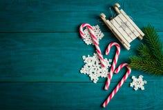 Bastoncini di zucchero di Natale, slitta del giocattolo, fiocchi di neve a foglie rampanti e rami dell'abete rosso Fotografie Stock