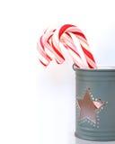 Bastoncini di zucchero dolci di Natale in una tazza grigio chiaro con un foro della stella Immagini Stock