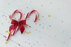 Bastoncini di zucchero e coriandoli su bianco Fotografia Stock