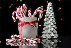 Bastoncini di zucchero ed alberi festivi di Natale sulla tavola riflettente Fotografia Stock