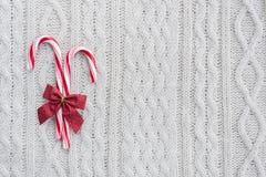 Bastoncini di zucchero su fondo tricottato bianco Immagini Stock Libere da Diritti