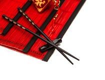 Bastoncini neri sulla stuoia di bambù rossa Nuovi anni cinesi di carbone fortunato Fotografia Stock