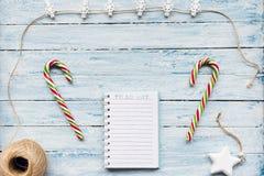 Bastoncino di zucchero e fare lista su un fondo blu e bianco immagine stock