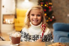 Bastoncino di zucchero sorridente della tenuta della bambina, esaminante macchina fotografica mentre Fotografia Stock