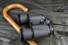 Bastone da passeggio e binocolo su un cappotto all'aperto Immagini Stock