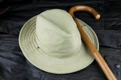Bastone da passeggio e cappello su un cappotto incerato all'aperto Fotografia Stock