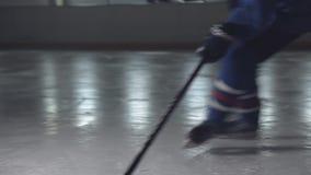 Bastone di hockey su ghiaccio che tratta i pattini pattinanti del giocatore del disco in un'arena archivi video