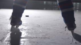 Bastone di hockey su ghiaccio che tratta i pattini pattinanti del giocatore del disco in un'arena video d archivio