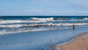 Bastone di legno che sta contro la spiaggia del mare del wavesnorth Immagini Stock Libere da Diritti