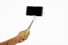 Bastone di Selfie con il telefono cellulare isolato su fondo bianco Fotografia Stock
