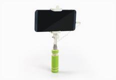 Bastone di Selfie con il telefono cellulare su fondo bianco Immagini Stock