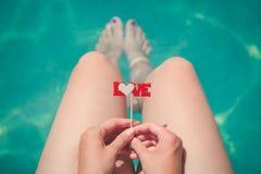 Bastone femminile della tenuta con il segno di amore al poolside Immagine Stock Libera da Diritti