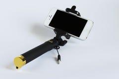 Bastone metallico del selfie con uno smartphone su un fondo bianco Fotografia Stock Libera da Diritti