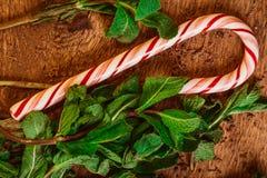 Bastones de caramelo con las hojas de menta en un fondo de madera Imagen de archivo libre de regalías