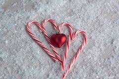 Bastones de caramelo con un ornamento del corazón Imagen de archivo