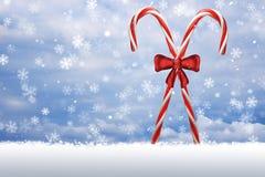 Bastones de caramelo cruzados en la nieve Imagen de archivo libre de regalías
